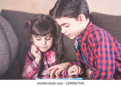 Kids using their tablet at home. Kids and technology concept