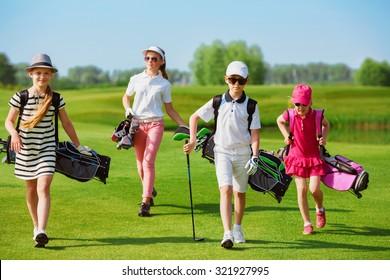 Kids walking on fairway with bags at golf school