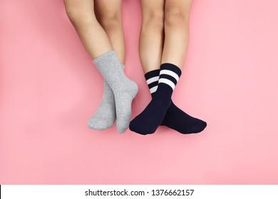 Kids wearing cute grey and black socks on pink background. Minimalism fashionable winter set.