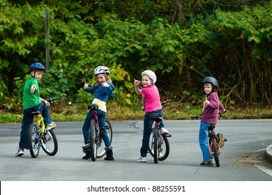 Kids wearing helmets on their bikes.  Riding on the street.