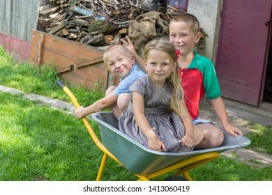 kids in wheelbarrow,two boys and a girl were sitting in a wheelbarrow in the summer, children are played by a wheelbarrow in the yard