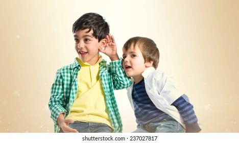 Kids whispering over ocher background