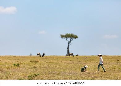 Kids witnessing great migration of wildebeests in Masai Mara National park in Kenya