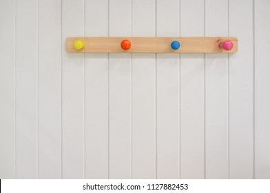 Kids wooden colorful hanger on white wall with copy space