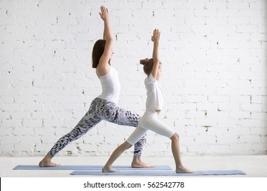 Kids yoga female teacher training girl child, practicing yoga, standing in Warrior one exercise, Virabhadrasana I pose, working out wearing sportswear, indoor full length, white loft studio background