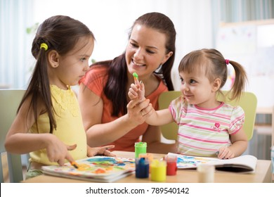 Kids with young teacher woman painting on table together in kindergarten or home.