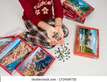 Kiev, Ukraine– April 11 2020 : Cheerful young woman putting jigsaw puzzle pieces during quarantine. Many puzzle boxes with the finished puzzle. Quarantine games. Stay at home concept.