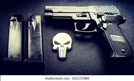 Kiev - July 15 2017: SIG Sauer P226 handgun with punisher patch on the black table.