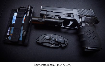 Kiev - Jun 15 2018: Weapons with everyday carry equipment on the wooden table. Sig Sauer P226 handgun.