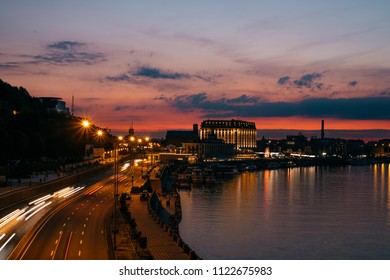Kiev Kyiv city, the capital of Ukraine at night with beautiful sunset clouds, colorful illumination and reflection in Dnieper Dnipro river. Long exposure traffic light.