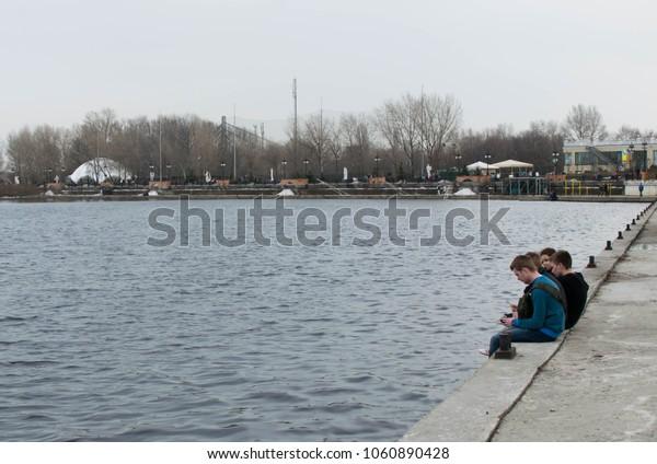Kiev, Ukraine - 01, April, 2018: teenagers are sitting on the parapet Obolonskaya embankment in Kiev in the spring