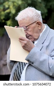 Kiev, Ukraine, 01.09.2012 A short-sighted gray-haired old man in glasses reads papers keeping them close to his eyes