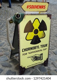 Kiev / Ukraine - 05 01 2018: paper sign on street tempting tourists to visit Chernobyl tour, sign with radioactive symbol and gas mask (translation of text in cyrilics: Top Chernobyl Tour)