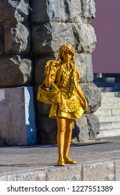 Kiev, Ukraine, 07 august 2018. Girl depicting a statue on a city street. A living statue painted in gold on the street.
