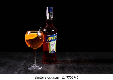 Kiev, Ukraine - 07 November 2018. Glass of Aperol Spritz cocktail with bottle of Aperol on stone table on the black background. Aperol is famous Italian aperitif.