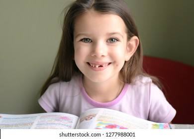 Kiev, Ukraine - 12.27.2018 little caucasian white beautiful long haired brunette girl reading a book. smiling toothless girl. Smiling cute kid without front milk tooth. Kid expression portrait