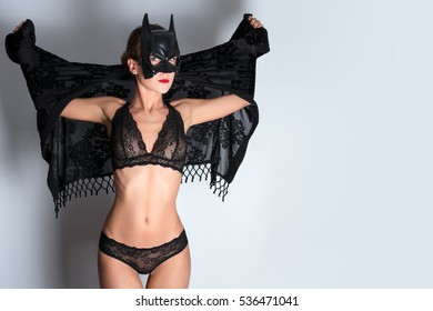 KIEV, UKRAINE - 2 DECEMBER, 2016: Young woman with slim athletic body in sexy black lace lingerie wearing batman mask. Batgirl posing on white background. Sex games, fashion studio shot
