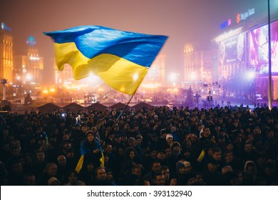Kiev, Ukraine - 24 November, 2013: Meeting on the Independence square at night in Kiev. Girl holding a flag of Ukraine. During revolution to support the integration of Ukraine into the European Union.