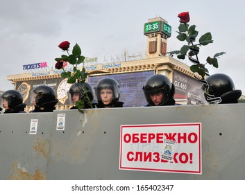 """KIEV, UKRAINE - 30 NOVEMBER 2013: Unknown police-officers under the poster """"Attention slipperiness"""" guard the Independence square after dispersal of meeting on November 30, 2013 in Kiev, Ukraine."""