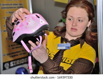 KIEV, UKRAINE - 6 MARCH 2013: Unknown woman presents a child helmet for a bicycle on the international bicycle exhibition on March 6, 2013 in Kiev, Ukraine.
