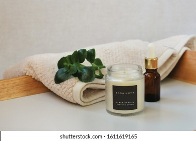 Kiev, Ukraine. 7 of January 2020. Candle Zara Home on a white background. The composition also consists of a brown bottle of cosmetics, lettuce leaves and a white terry bath towel