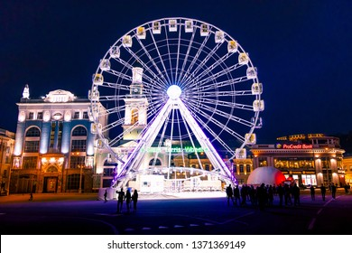 Kiev, Ukraine; 9 April 2019; a view of a ferris wheel and the Bell Tower of the Orthodox Church of St. Catherine the Great Martyr, located at the Contract Square at night