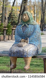 KIEV, UKRAINE - APRIL 10 2017: Sculpture of an old woman sitting on the bench is situated in the park. KIEV, UKRAINE - APRIL 10 2017.