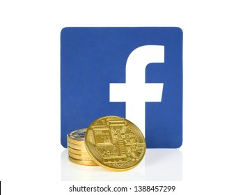 Kiev, Ukraine - April 10, 2019: Facebook icon printed on paper and placed with cryptocurrency coins. Facebook develops its own Cryptocurrency for remittances