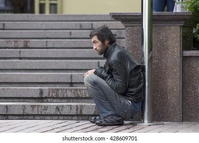 Kiev, Ukraine - April 11: Poor homeless man is sitting on the ground, on April 11, 2016 in Kiev, Ukraine