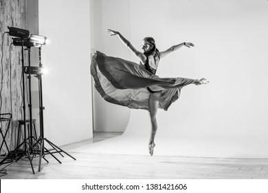 KIEV, UKRAINE - April 2019: Beautiful ballerina girl dancing in the photo studio. Photo shooting of ballerina dancer, Kiev, Ukraine. Black and white picture.