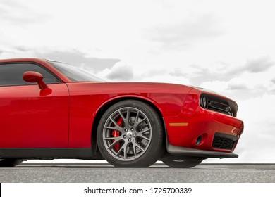 Kiev, Ukraine - April 21, 2020: Muscle car Dodge Challenger SRT8 392 HEMI against the sky. Red car on sky background