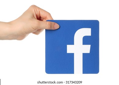 KIEV, UKRAINE - APRIL 30, 2015: Hand holds facebook logo printed on paper on white background. Facebook is a well-known social networking service.