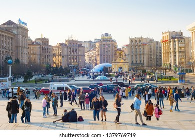 KIEV, UKRAINE - APRIL 6, 2019: Crowd of people walking at Maidan Nezalezhnosti central square in sunlight, cars traffic and shopping mall Globus glass rooftops, Kyiv, Ukraine