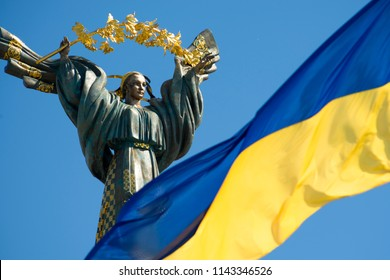 Kiev, Ukraine - August 05; 2017: Monument of Independence - a column with a figure of a woman with a branch of a guelder-rose on her hands. In the foreground the Ukrainian flag (blur focus)