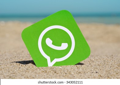 KIEV, UKRAINE - AUGUST 10, 2015: . WhatsApp proprietary messenger for smartphones printed on paper and placed in the sand against the sea.  Allows you to send text messages, images, video and audio.