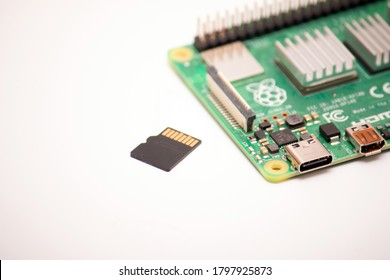 Kiev, Ukraine - August 13th, 2020:A micro SD card with the operating system installed lies next to the Raspberry Pi 4 single-board computer on a white background.