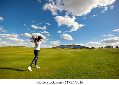 KIEV, UKRAINE - AUGUST 19, 2018: Women player golf swing shot on course. Girl golf player with driver teeing-off from tee-box to shoot. Space for text, background.