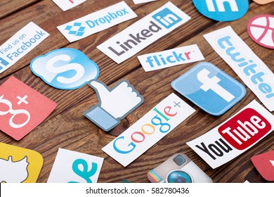 KIEV, UKRAINE - AUGUST 22, 2015:Collection of popular social media logos printed on paper:Facebook, Twitter, Google Plus, Instagram, Pinterest, Skype, YouTube, Linkedin others on wooden desk