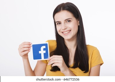 KIEV, UKRAINE - August 22, 2016: Woman hands holding facebook icon sign printed on paper on white background. Facebook is a well-known social networking service.