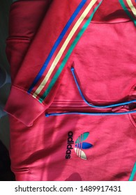 KIEV, UKRAINE - AUGUST 28, 2019: Adidas logo embroidered on a red sports jacket.