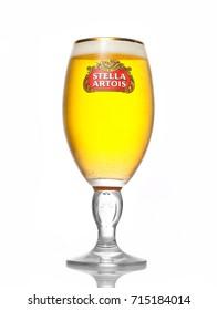 Kiev, Ukraine - August 3, 2017:Cold glass of Stella Artois beer on white background, prominent brand of Anheuser-Busch InBev, is a pilsner brewed in Leuven, Belgium, since 1926