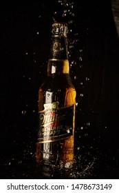 Kiev, Ukraine - August 3, 2019: Miller beer on a black wet background in spray of water. Beer miller with drops of water in the air. Bottle of Miller Beer.