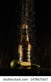 Kiev, Ukraine - August 3, 2019: Miller beer on a black wet background in spray of water. Beer miller with drops of water in the air and lime. Bottle of Miller Beer with Lime.