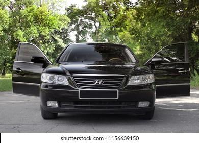 Kiev, Ukraine - August 6, 2018: Hyundai Grandeur on the forest road. Black car with open doors