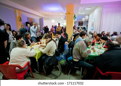 KIEV, UKRAINE - DEC 10: Poor people sit around tables with food at the Christmas charity dinner for the homeless on December 10, 2013, in Kyiv, Ukraine. About 100,000 adults are homeless in Ukraine.
