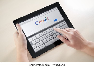KIEV, UKRAINE - DECEMBER 03, 2011: Woman holding Apple iPad with Google search web page on a screen. This second generation of Apple iPad is designed and development by Apple inc. in march 2011.