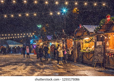 KIEV, UKRAINE - December 2018: Christmas market in Kiev, people on the market tasting food and hot wine, Kiev, Ukraine. Snow effect added.