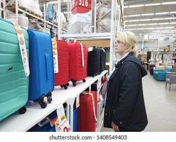 Kiev, Ukraine, Europe - May 2019: A girl chooses a suitcase for trips in the market. Suitcases for tourism are on the counter of the supermarket Auchan.