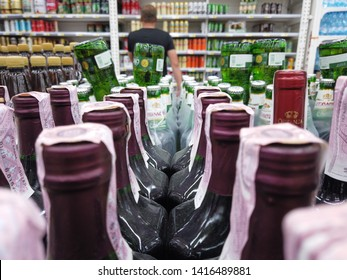 Kiev, Ukraine, Europe - May 2019: Showcase with bottles of alcoholic beverages in the Auchan supermarket. Alcohol trade in the market. Wine.
