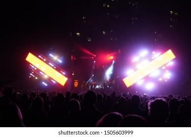 "Kiev, Ukraine, Europe - September 15, 2019: Many spectators in front of the stage. Open air music festival ""SolomaFest"". Fans dance in front of the stage at the concert. Stage lights blink."